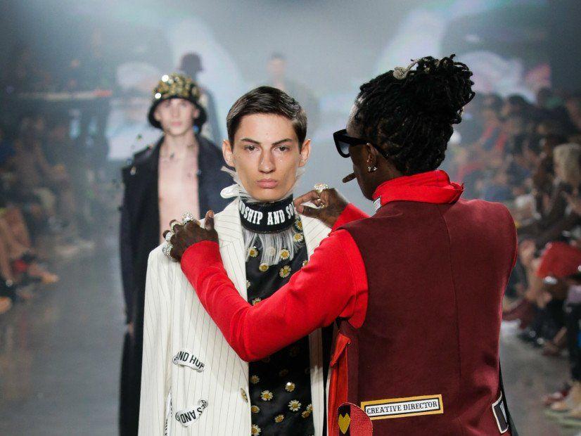 Young Thug beugt Modemuskeln und passt das Outfit des Models in der Mitte des Laufstegs an